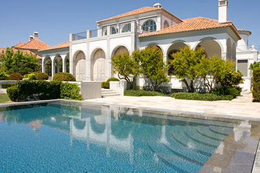 Large white mansion with a huge pool.